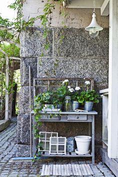 LITE HJØRNE: Et lite bord ved inngangspartiet kan dekoreres etter sesong og sørge for en hyggelig velkomst. Her har eieren brukt planter og potter, og i bakkant står et gammelt vindu som en slags ramme.