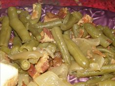 CROCK POT GREEN BEANS  4 cans green beans, drained   2 (7 oz) cans chicken broth, seasoned with roasted garlic   1/2 onion,cut into 6 wedges   1/4 lb bacon, cut into small pieces and semi fried   salt & pepper  Add everything into crock pot and mix.  Cook on low for 2 hours.
