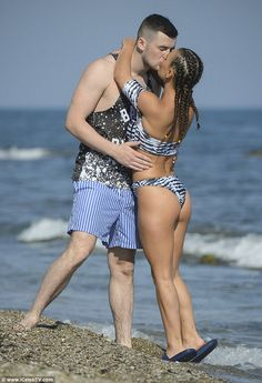 Smitten again: Tommy, dressed in a black and white vest and blue striped shorts, couldn't keep his eyes or hands off Chantelle