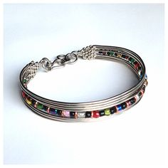Zee Bee Market LLC - Silverplated Wire Beaded Bracelet. This classic silverplated copper wire bracelet features a row of multi-colored beads and finely woven, flattened ends. The bracelet features a hook clasp and is adjustable. Handmade by Fair Trade artisans in Kenya.