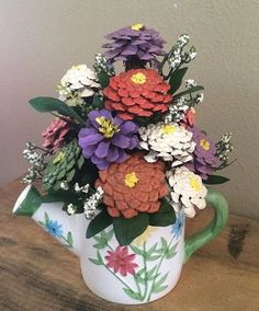 Pine cone flowers in ceramic watering can  planter