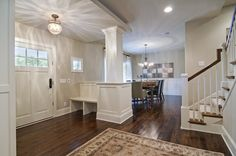 with front door opening directly in to living room, half-height column and bench 'fakes' a foyer