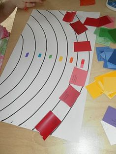 Using paint chip cards, to make a rainbow in colour order.