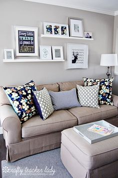 Above the couch simple plank floating shelves. Uses large frames mounted on the wall an small picture frames propped up on the shelves.