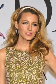 Curl hair with a large-barrel curling iron and brushing curls out, and wear a headband of your choice—we love Blake's pastel ribbon band. For added volume, tease the hair behind the headband. #hairstyles #blakelively
