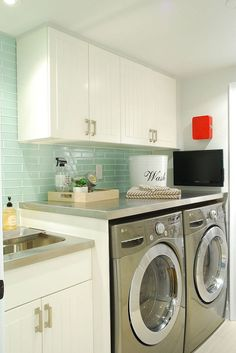 Pretty & practical, this laundry is made to look larger with reflective stainless steel counters & glass tiles.