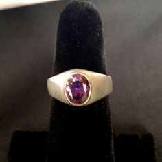 VINTAGE 1970s Brushed Silver & Amethyst Band Ring A thick brushed silver band almost a half inch wide at its widest point. The dark purple oval cut amethyst is almost that long, covering the entire face of the ring. Beautiful clear dark stone sparkles beautifully. Stamped 925. Very good vintage condition. No scratches. Vintage Jewelry Rings