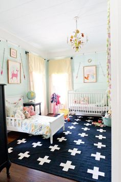 Light aqua shared girl's bedroom with wonderful pastel accents, globe, arrows and floral chandelier.