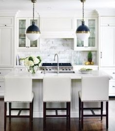 at home kitchen white nailhead trim barstools cararra marble subway tile backsplash hick pendant lights blue gold crown molding top cabinets dark wood floors