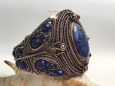 A beautiful sodalite (cut by Jámbor László) is in the centre of this multilayered cuff bracelet adorned with a lot of different size and shape lapis lazuli accent beads. The frame of the bracelet is sawed from copper sheet and I layered plain and twisted wire to create this beautiful piece
