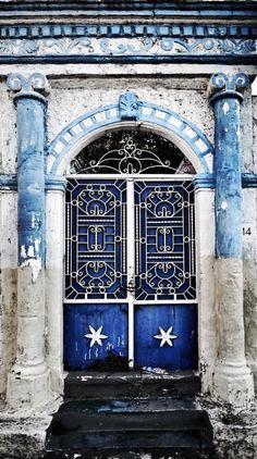 Beautiful stone work around blue doors in Agioi, Anargyroi, Athens, Greece.