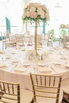 Elegant reception in pale pink and gold with tall centerpiece table decor