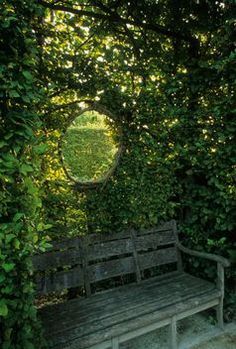 Round window in hedge above bench. Jardins du Prieure, Notre Dame d Orsan, France.