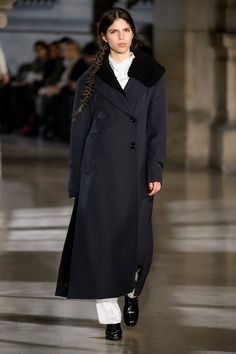 12. Wadded trench-coat in high density wool gabardine, pointed collar shirt, highneck tee-shirt and two-pleated pants in viscose satin, clogs in leather