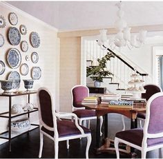 dining rooms - white decorative plates art wall decor tiered iron console table French purple velvet dining chairs round wood dining table milk-glass white chandelier espresso wood floors sand beige grasscloth grass cloth wallpaper