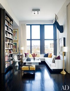 In designer Jamie Drake's New York City living room, a custom cocktail table and a sectional sofa are joined by a Pedro Friedeberg Hand chair, a 1950s lacquer low chair, and gold-leafed floor lamps.