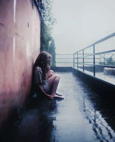 chica sentada sola frente edificio