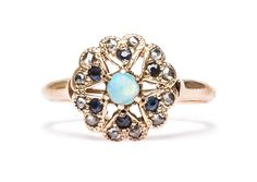 The Victorian Opal Ring is a lovely vintage engagement or right hand rind centering a round, white opal surrounded by a starburst of sapphires and diamonds set in hand pierced heart-shaped settings. This unique cluster ring is unique and unmistakably vintage - with a lovely price tag to match! | Trumpet & Horn | $750