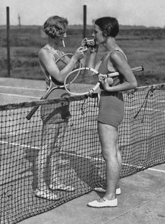 Two women lighting cigarettes on a tennis court in Essex, England c.1930's.