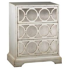 "Reminiscent of Old Hollywood style, this weathered chest features 3 drawers with circular fretwork overlay.   Product: ChestConstruction Material: Wood and mirrored glassColor: Weathered ivory  Features: Three drawersAntiqued mirrored fronts with fretwork overlay Dimensions: 29"" H x 24"" W x 15"" D"