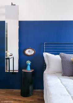 Parede pintada de azul royal, cama de ferro e tronco usado como criado mudo.