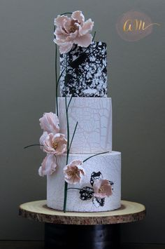 Modern black, white, and blush cake with three tiers of differing crackled marble designs. The soft pink flowers with sharp green stems accent this wedding cake perfectly!     Cake Design: Cakes by Angela Morrison