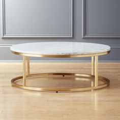 Shop Smart Round Marble Brass Coffee Table. Open cylinder construction of brass-plated steel topped with a Carrara-style white/grey slab. Low-profile and sleek, this marble brass coffee table vibes beautifully with any style. CB2 exclusive.