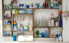Take the bottoms out of crates and mount them as open shelving in a kitchen. An eclectic selection of tableware will help to add life to the look. Source