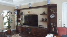 Quality built wall unit with many different design aspects.  A mix of traditional and modern cabinet styles.  entertainment center with floating shelves and fixed curved shelves. Quality cabinetry from Alliance Cabinets & Millwork Inc.