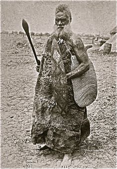 Aboriginal elder in possum skin cloak and woven string bag, with spear. Victoria. late nineteenth century.