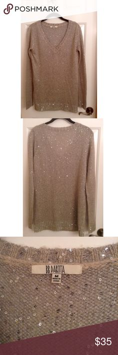 """LAST CHANCE BB Dakota Sequin V-Neck Sweater BB Dakota v neck sequin sweater.  Like new.  Tunic length.  Color is a light gray/beige with silver metallic thread and sequins for sparkle.  Measures approximately 28.5"""" from shoulder.  Size Medium.  Perfect for the holidays.  51% Acrylic, 34% Nylon, 15% Mohair.  Hand wash cold.  Lay flat to dry. BB Dakota Sweaters V-Necks"""