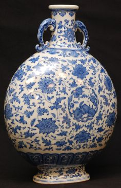 CHINESE QIANLONG BLUE & WHITE PORCELAIN MOON FLASK - Chinese blue and white hand painted porcelain moon flask handled vase depicting flowers with scrolled stems throughout. Paddle border. Holds Ching Dynasty Qianlong (1736-1795). Measures 13 1/2 height x 10 1/2 width (34.3cm x 26.7cm).