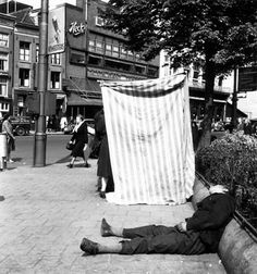 1947. Man sleeping at the Rembrandtplein in Amsterdam. In the background lunchroom Heck's. Photo MAI Beeldbank / Sam Presser. #amsterdam #1947 #Rembrandtplein