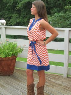 NAVY & ORANGE CHEVRON PRINT GAMEDAY DRESS WITH BRA-FRIENDLY SLEEVES AND TIE BELT. BE THE CUTEST GIRL AT THE TAILGATE IN THIS COMFY DRESS! $49 PAIR WITH OUR TAN COWGIRL BOOT TO FINISH THIS LOOK OFF. GET YOUR GAMEDAY DRESS WHILE THEY LAST, LIMITED QUANTITY!!