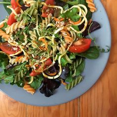 Salad with spinach, tomato, pasta, carrot, zucchini, fresh herbs, seeds and honey mustard olive oil vinagre dressing