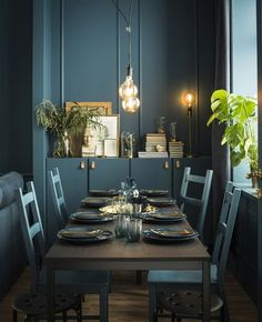 A dining table and chairs are custom painted in the same shade of green, and set with tableware in a similar color.