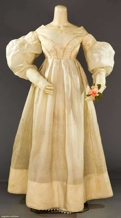 "WHITE ORGANDY EMPIRE GOWN, LATE 1830s Lot: 196 May 9, 2017 - CATALOG SALE Sturbridge, Massachusetts 1 piece, pleated & banded upper sleeves, 2 curving ruched bands on bodice, lace trimmed cuffs, box pleated skirt, B 32"", Hi W 25"", L 52"", (all over foxing, few untacked shoulder pleats) very good."