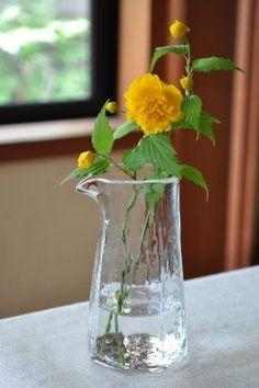 yellow flower in handmade glass jug