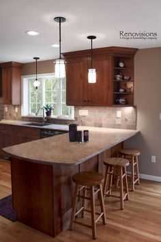 Kitchen remodel by Renovisions. Cherry cabinets, shaker cabinets, under cabinet lights, tuscan-clay-look porcelain tile backsplash, quartz countertop, peninsula, corner open shelves, pendant lights, recessed lights. Rockwell Catering and Events