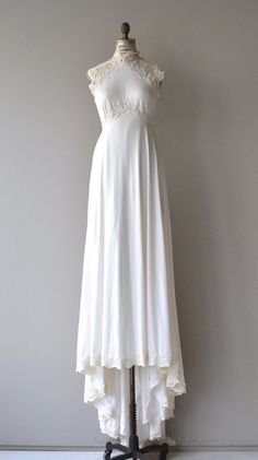 Vintage 1970s white wedding gown in very comfortable jersey knit with high lace neckline and shoulders, lace cap sleeves, lace insert empire waist,