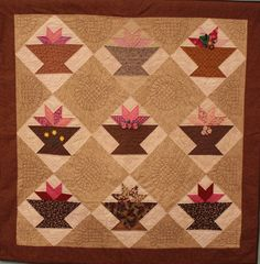 "Florida Baskets    Lap Quilt 01    ""I won most of the blocks in a Block of the Month raffle in July 2009. For the quilting I used two techniques, straight line echo quilting around the smaller pieces, with freehand drawn flowers and leaves in the larger rectangles. I used #5 perle cotton thread for the quilting."""