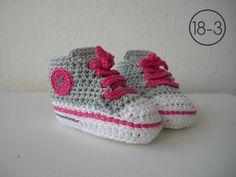Zapatillas a ganchillo con suela blanca, base en gris y cordones y detalles en color fucsia.