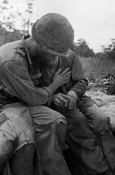 An unidentified soldier breaks down under the stress of combat and is comforted by a comrade following recent battle 55 miles west of Pleiku, South Vietnam, 1967, unattributed photo