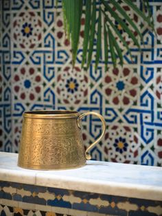 Traditional ornate tiled fountain in Morocco  A brass cup at a drinking fountain