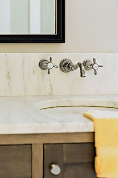Wall-mount faucets make it easy to clean the marble counter with a swipe. The sink cabinet has a warm, gray-washed finish for a reclaimed-wood look. Faucet: Moen