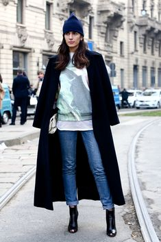 We love the glam Milan take on this jeans and sweatshirt ensemble with an elegantly draped coat and a whimsical veil fastened to her beanie. #streetstyle