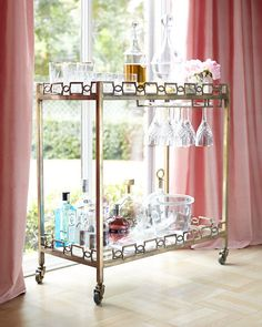 """Handcrafted bar cart. Linked gallery-framing on both top and bottom shelves. Made of forged iron and tempered glass. Brass-patina finish. Two shelves. Stemware hanger and rolling casters. 32""""W x 16""""D"""