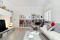 shelves, low table, sofa....nice combo of scale. I dig this living room. I need book space.