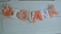 Móbile de letras horizontal para enfeitar a porta da maternidade ou do quarto do bebê. Letras confeccionadas em tecido de algodão e feltro com enchimento de fibra siliconada, no tamanho de mais ou menos 4,5 cm largura e 8 cm de altura, cada. O preço por letra é de R$ 5,00, com as flores de enfeite incluídas.