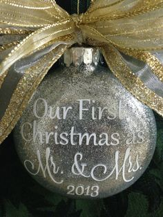 This 3 1/2 (flattened M&M shape) glass ornament is hand glittered on the inside. The one in the picture is done in silver. The wording is done in high quality vinyl and says Our First Christmas as Mr. & Mrs. 2016. Names are added to the back of the ornament. I can do this in silver, red, or green glitter. All writing will be done in white. A coordinating bow will be added to the top of the ornament (my choice). In notes to seller at checkout, please leave the names to be added to the back of…